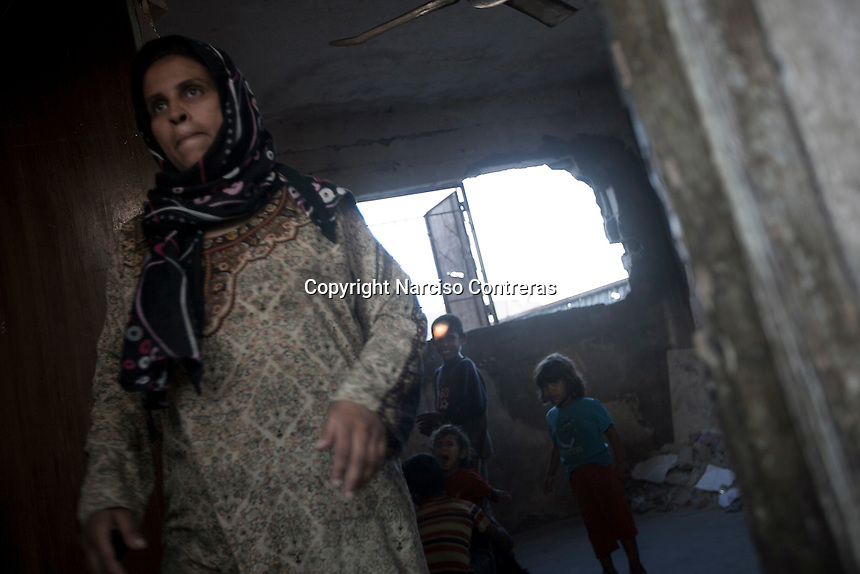 "In this Saturday, Aug. 16, 2014 photo, a Palestinian family is seen at the entrance of their house after it was damaged by artillery shelling during the ""Protective Edge"" Israeli military operation in Beit Hanoun neighborhood in Gaza City. After a five days truce was declared on 13th August between Hamas and Israel, civilian population went back to what remains from their houses and goods in Gaza Strip. (Photo/Narciso Contreras)"