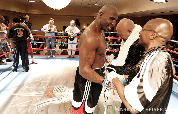 Tallahassee fighter Travis Walker, third from right, smiles at his trainer, Dwight Pratchett, right, and Richard Wood as they remove his boxing gloves after he defeated Andrew Greeley, from Monroe LA, in a 10 round boxing match at the DoubleTree Hotel in Tampa August 19, 2006.