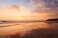 The peaceful waters of Kaua'i's Kealia Beach Park reflect the gentle hues of a golden sunrise lightening a cloudy blue sky.