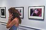 A young woman talking on a cell phone is standing in front of a photograph of a young woman talking on a cell phone, 'It's Not Me' by artist Jie Gen, at the Fotofoto Gallery Opening Reception of the 2013 'Under The Influence' Student Invitational Exhibition. On display were images of 29 photography students of instructors from fotofoto, the event venue.