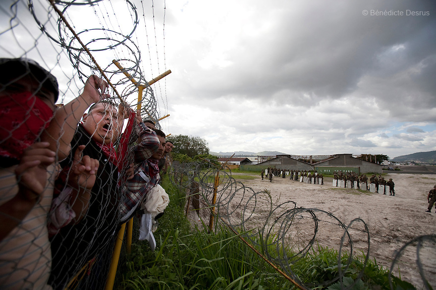 5 July 2009 - Tegucigalpa, Honduras - Supporters of ousted Honduras' President Manuel Zelaya wait at a border fence of the international airport in Tegucigalpa. One of them chants at the soldiers. Zelaya turned back from an attempted return home on Sunday after soldiers clashed with his supporters as he tried to land, fueling tensions over the coup that toppled him. At least one person was killed and ten were badly wounded when protesters demanding the return of ousted Honduran President Manuel Zelaya clashed with troops at the Tegucigalpa airport. Photo credit: Benedicte Desrus