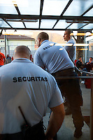 Switzerland. Canton Ticino. Chiasso. A group of men seat outside in a courtyard of a centre for immigrants.They all.are economic migrants and have asked for political asylums in Switzerland. They are now waiting for the answers from the swiss government. Inside the centre, they are controlled by security guards working for Securitas, a private company, under contract and paid by the swiss Federal Office for Migration. 08.04.11 © 2011 Didier Ruef