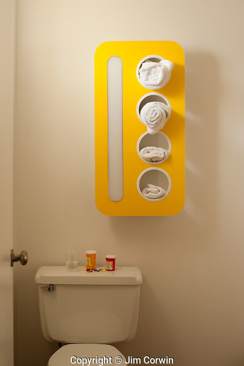Bathroom with towel rack and pill bottles on back of toilet,