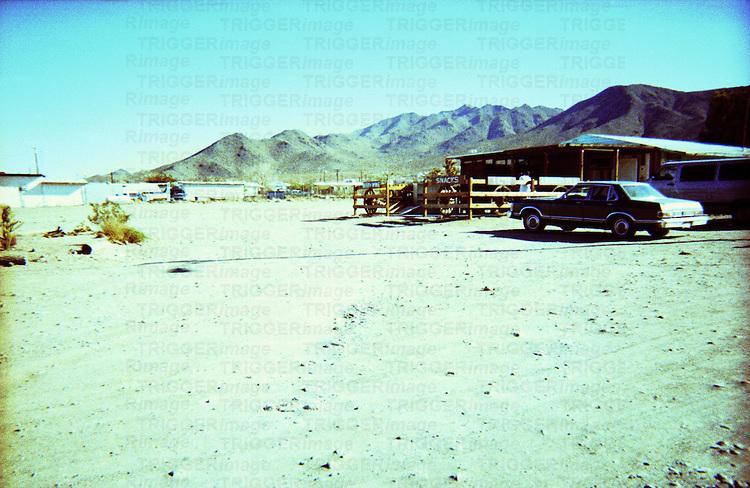 An american desert scene with farm buildings and a car