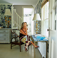 Designer Jacqueline Coumans sits on a Chinese horseshoe chair and looks out onto her garden