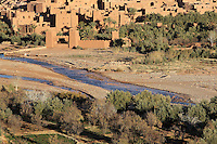 Oued Marghen river and Ksar Ait Ben Haddou, earthen fortified city, Ounila valley, Ouarzazate province, Morocco. The ksar is a group of earthen houses surrounded by high defensive walls with corner towers, in traditional pre-Saharan style.  The village is in the High Atlas and was a stop on the caravan route from the Sahara to Marrakech. It was founded in the 17th century and has been a UNESCO World Heritage Site since 1987. Picture by Manuel Cohen