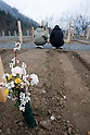 Onagawa, Japan - A photo made available on April 11 shows offerings at a temporary mass grave for the March 11 earthquake and tsunami victims. Yoshikatsu was visiting a friend at the time the earthquake hit and he quickly rushed back home to later see his wife and mother in front of the house thinking how to escape. Before the two could react to a plan to escape, the 10-meter tsunami swept them away, leaving Yoshikatsu to live. His son is still missing and continues to search for him everyday. (Photo by Christopher Jue/AFLO) [2331] **ITALY OUT**