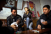 """Factory boss Mr Huang (top left corner) plays cards with fellow bosses and their wives at his home in Zhongshan city, China..This picture is part of a photo and text story on blue jeans production in China by Justin Jin. .China, the """"factory of the world"""", is now also the major producer for blue jeans. To meet production demand, thousands of workers sweat through the night scrubbing, spraying and tearing trousers to create their rugged look. .At dawn, workers bundle the garment off to another factory for packaging and shipping around the world..The workers are among the 200 million migrant labourers criss-crossing China.looking for a better life, at the same time building their country into a.mighty industrial power."""