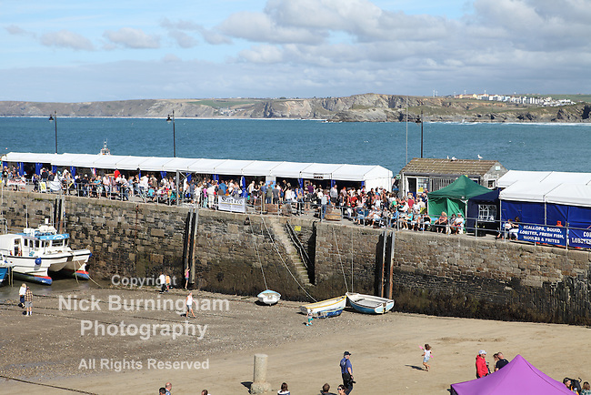 NEWQUAY HARBOUR, NEWQUAY, UK - SEPTEMBER 17, 2016: Crowds of people attend the Newquay Fish Festival in the 300 year old harbour.  Stalls offer various seafoods and local crafts.