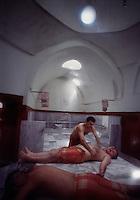Men lie on a marble floor in a public bath getting massages.