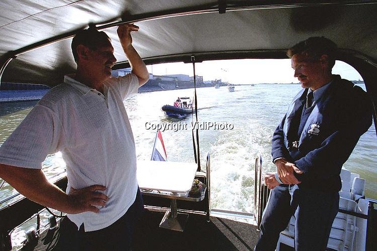 Foto: VidiPhoto..NIJMEGEN - Agenten van de politie te water (KLPD) controleren een jacht op de Waal. Het scheepvaartverkeer op de grote rivieren wordt steeds drukker, door onder meer de toename van de recreatievaart. De beroepsvaart heeft daar veel last van. De KLPD wil daarom dat het vaarbewijs ook verplicht wordt voor jachten beneden de 15 meter. De Hiswa onderzoekt op dit moment de knelpunten tussen beroeps- en recreatievaart op de grote rivieren.