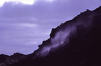 ISLANDA: paesaggio vulcanico. Del vapore fuoriesce dalla costa di una montgana. Dietro un cielo nuvoloso.