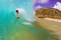 A bodysurfer rides the barrel at Oahu's Sandy Beach.