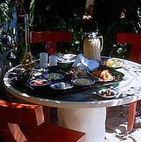 A garden table in a shady corner of the terrace is set for lunch with a tray of local delicacies