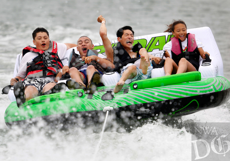 STAFF PHOTO JASON IVESTER --06/07/2014--<br /> Brothers Jesse Barrientos (left), 16, and Jonathan Barrientos (second from left), 19, and their sister Isabel Barrientos (right), 11, all of Rogers, and Andy Tu of Fayetteville hang on as they ride behind a boat on Saturday, June 7, 2014, on Beaver Lake. Sources for Community Independent Living Services hosted its 16th annual Fun Day on Beaver Lake for residents with disabilities.