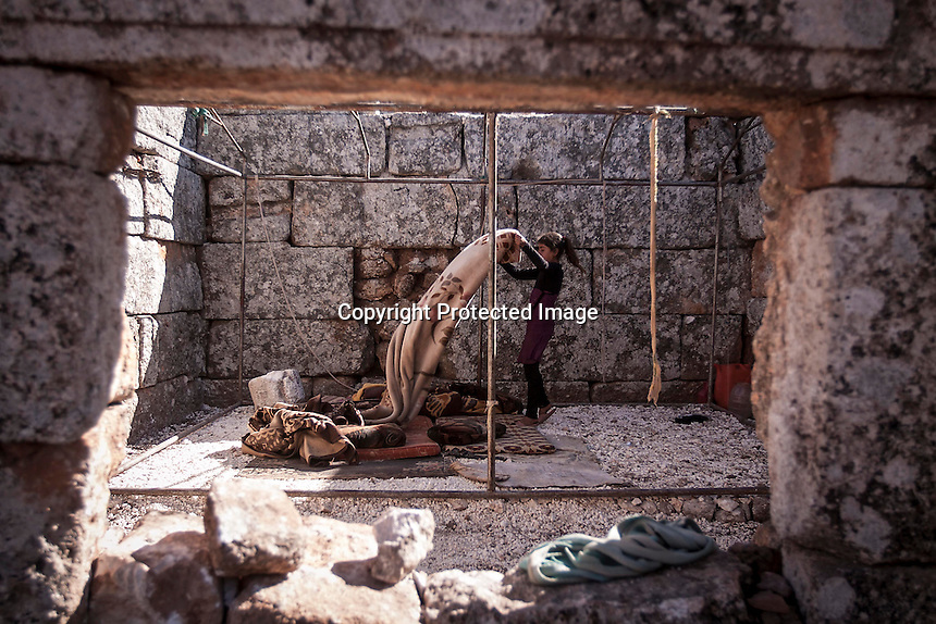 "In this Friday, Sep. 27, 2013 photo, a Syrian displaced girl cleans her bed after she waked up at the Kafr Ruma, an ancient roman ruins used as temporary shelter by those families who have fled from the heavy fighting and shelling in the Idlib province countryside of Syria. Dozens of families settled in the ancient ruins known as ""The Forgotten City"" and declared human heritage by UNESCO, when the clashes between opposition fighters and government forces broke out in the region since more than two years ago. (AP Photo)"