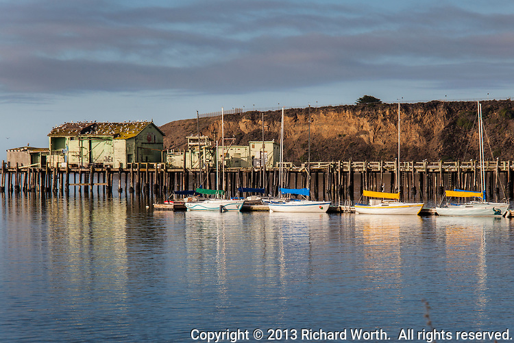 The old Romeo fishing pier and cannery, festooned with gulls, with four sail boats, sails furled,  Princeton-by-the-Sea, Half Moon Bay, California.