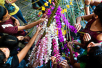 "Salvadoran girls decorate coconut palm fronds with flower blooms during the Flower & Palm Festival in Panchimalco, El Salvador, 8 May 2011. On the first Sunday of May, the small town of Panchimalco, lying close to San Salvador, celebrates its two patron saints with a spectacular festivity, known as ""Fiesta de las Flores y Palmas"". The origin of this event comes from pre-Columbian Maya culture and used to commemorate the start of the rainy season. Women strip the palm branches and skewer flower blooms on them to create large colorful decoration. In the afternoon procession, lead by a male dance group performing a religious dance-drama inspired by the Spanish Reconquest, large altars adorned with flowers are slowly carried by women, dressed in typical costumes, through the steep streets of the town."