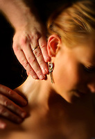 Male hands massaging female's neck.<br />