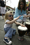 Two-year-old Mackenzie Ziegler plays the Bongo Drums with her mother, Julie Ziegler, in the 21st annual Summer Solstice Parade held Saturday, June 20, 2009 in Seattle, Wa. The parade was held Saturday, bringing out painted and naked bicyclists, bands, belly dancers and floats. (Jim Bryant Photo © 2009).. .