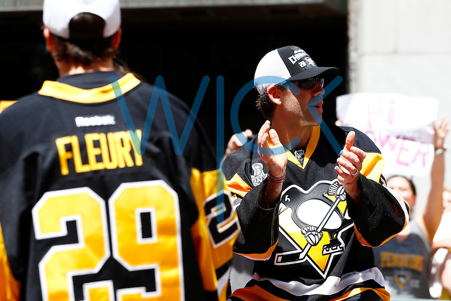 Pascal Dupuis #9 and Marc-Andre Fleury #29 of the Pittsburgh Penguins ride along Grant Street during the Stanley Cup victory parade in downtown Pittsburgh, Pennsylvania on June 15, 2016. (Photo by Jared Wickerham / DKPS)