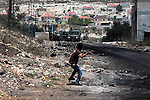 A Palestinian protester throws stones towards Israeli soldiers during clashes following a protest against the expropriation of Palestinian land by Israel on March 31, 2013 in the village of Kfar Qaddum, near the occupied West Bank city of Nablus. Photo by Nedal Eshtayah