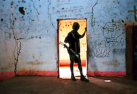 ©Sven Torfinn/Panos Pictures..South Sudan, 2001.Upper Nile region, village of Gorgial, Christian church blotted and damaged by the GOS (government of Sudan) army in the fighting between North and South Sudan, SPLA armed soldier standing in the doorway