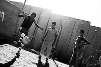 Palestinian boys play football on a school pitch in front of the controversial Israel separation barrier in the West Bank village of Anata, on the outskirts of Jerusalem on June 8, 2010.© ALESSIO ROMENZI