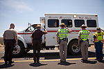 Law enforcement personnel salute as the Granite Mountain Hot Shots vehicles are brought out of the Yarnell Hill Fire, July 3, 2013 after 19 of their crew died in the fire Sunday.