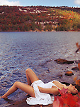 Sensual, romantic photo of a  young woman in white dress lying on a rocky lake shore. Fall nature scenic.