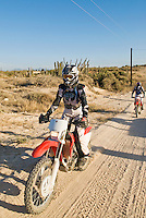 Female motorcycle rider on dirt road in Baja, Mexico