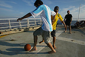 Playing football on the helicopter deck of the Greenpeace ship MV Arctic Sunrise.PIC © JEREMY SUTTON-HIBBERT 2002.
