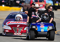 Nov 12, 2010; Pomona, CA, USA; NHRA pro stock team owner Ken Black (left) rides in a gold cart towing the car of Greg Anderson during qualifying for the Auto Club Finals at Auto Club Raceway at Pomona. Mandatory Credit: Mark J. Rebilas-