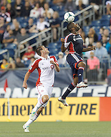 Toronto FC substitute forward Justin Braun (17) and New England Revolution defender Andrew Farrell (2) battle for head ball.  In a Major League Soccer (MLS) match, Toronto FC (white/red) defeated the New England Revolution (blue), 1-0, at Gillette Stadium on August 4, 2013.