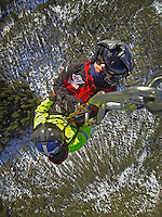 Crew from Norwegian Air Ambulance practice rescue skills at Camp Torpomoen, a training facility...Pilot and rescue paramedic hang below a helicopter during pick up training.