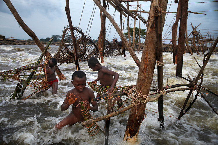Children check small versions of the bamboo baskets their fathers use, at Wagenia Falls on the left bank of the Congo River, near Kisangani, DR Congo.