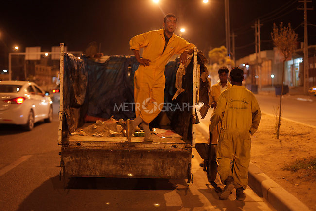 10/10/2014 -- Kirkuk, Iraq -- Bangladeshi workers clean the street at night in Iskan neighborhood in north Kirkuk.