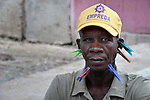 A man plays dominoes in Batey Bombita, a community in the southwest of the Dominican Republic whose population is composed of Haitian immigrants and their descendents. The clothespins are used to keep track of the score. This man is losing.