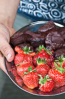A plate of  ChocoSol's chocolate and large red Cabot strawberries.