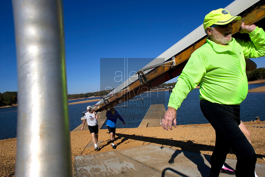 Jack Quigley (front to back), Kim Johnson, Peter Ewing and Randy Johnson carry a boat up an exposed section of lake bed at the Lake Lanier Rowing Club. Quiqley said low water levels have altered previously safe rowing routes on the lake.