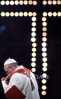 Pope Francis holds the wooden cross during the Via Crucis (Way of the Cross) torchlight procession on Good Friday in front of the Colosseum in Rome.April 18, 2014