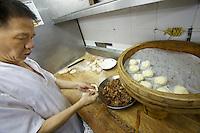 China, Hong Kong S.A.R..Dim Sum at Lin Heung Tea House, a traditional dim sum restaurant..Making of pork dim sum.