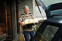 Putting the previous day's cheeses into the car to take them up the road to the cheese store...Cowherd and cheesemaker spends 100 days in the summer, high up in the mountains, tending cows and pigs and making cheese at Balisalp and Käserstatt near Meiringen, Switzerland.