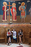 "Romania. Iași County. Iasi. Three gossiping girls seated on wooden chairs and three saints in the orthodox church ""Saint Nektarios"". Iași (also referred to as Iasi, Jassy or Iassy) is the largest city in eastern Romania and the seat of Iași County. Located in the Moldavia region, Iași has traditionally been one of the leading centres of Romanian social, cultural, academic and artistic life. The city was the capital of the Principality of Moldavia from 1564 to 1859, then of the United Principalities from 1859 to 1862, and the capital of Romania from 1916 to 1918. 6.06.15 © 2015 Didier Ruef"
