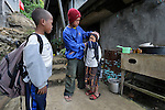 In the northern Philippines city of Baguio, Rolli Dulatre washes the face of his son Niño, age 9, while his brother Ryan, age 10, looks on, as the boys prepare to go off to school. Their mother, Rosielyn, left in November 2007 to work as a domestic worker in Hong Kong. Yet she soon landed in jail after a dispute arose with her employer, and the Bethune House Migrant Women's Refuge came to her assistance. She went to Hong Kong to earn money for her family's survival, and with the dream of eventually buying a small plot of land to farm. Rolli's earnings as a porter in the market don't even cover the monthly rent on their simple house on the edge of the city.