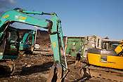 Diggers clean up the devastation caused by the earthquake and tsunami of March 11th 2001 beside a four storey building which has been knocked onto it's side by the tsunami, in Onagawa, near Ishinomaki, Japan, on Friday 17th February 2012.