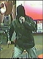 BNPS.co.uk (01202) 558833<br /> Picture: CCTV/BNPS<br /> <br /> Is this the worst ever police appeal?<br /> <br /> Optimistic detectives are asking the public to identify an armed robber - using a picture in which his face is completely concealed.<br /> <br /> The attacker pulled down a black woollen beanie hat over his face so it was completely hidden before entering a Labdrokes betting shop in West Moors, Dorset.<br /> <br /> Barely able to see through the makeshift mask, the robber approached the woman cashier wielding a knife before making off with notes from the till.<br /> <br /> Police studied CCTV footage of the raid and have now released images with an appeal to people to help identify the seemingly unrecognisable man.