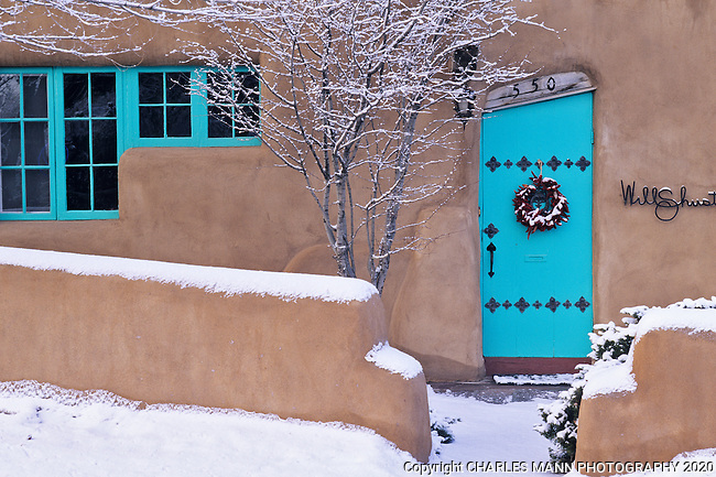 The home of Will Schuster, one of the famous Cinco Pintores group of Santa Fe painters, features turquoise colored door with a quirky shape which is especially colorful covered with a winter dusting of winter snow.
