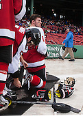 Matt Benning (NU - 5) helps Mike Gunn (NU - 6) with his skateguards. - The Northeastern University Huskies defeated the University of Massachusetts Lowell River Hawks 4-1 (EN) on Saturday, January 11, 2014, at Fenway Park in Boston, Massachusetts.