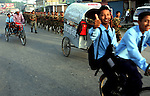 Children on their way to school pass members of the Nepalese army taking morning exercise on the streets of Dhangadhi, in western Nepal, on June 17, 2006. (Photo/Scott Dalton)